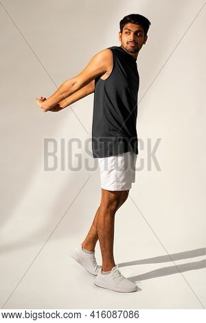 Man stretching in navy tank top and shorts sportswear apparel full body