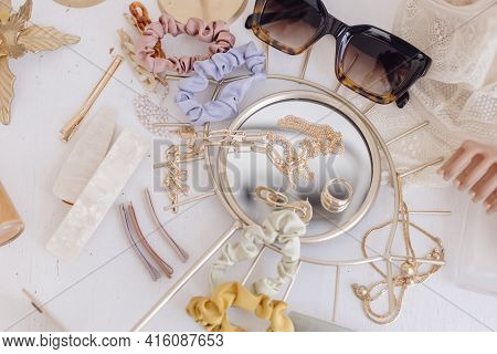Golden Jewellery, Sunglasses, Hair Clips, Cosmetics, Perfume And Lace Lingerie On White Table With V
