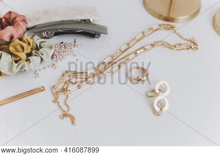 Modern Golden Jewellery, Hair Clips, Barrettes On White Table. Stylish Gold Ring, Chain Necklace, Ea