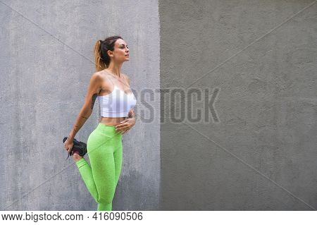 Sporty Woman Stretching Before Exercising Outdoors.