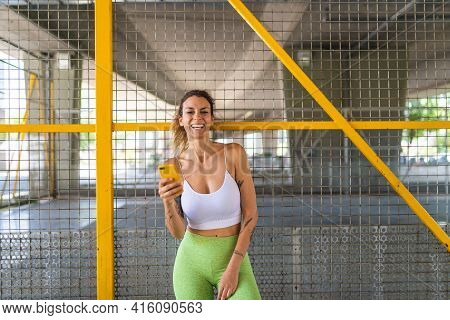 Sporty Woman Using Phone After Exercising Outdoors.
