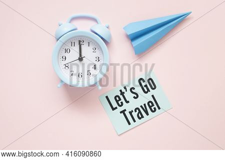 Let's Go Travel Text On Paper With Clock And Paper Airplane On A Pink Table.