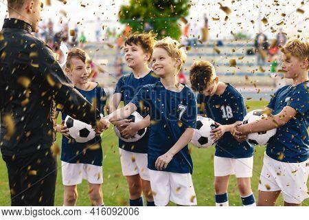 Happy Kids Celebrating Sports Success. Young Coach Congratulating To Boy Winning Football Soccer Tou