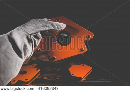 A Man's Hand Holds A Magnetic Angle For Welding Metal Constructions With A Fixed Angle Value. Studio