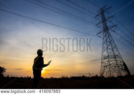 Silhouette Of Electrical Engineer Or Technician Standing And Watching At The Electric Power Station