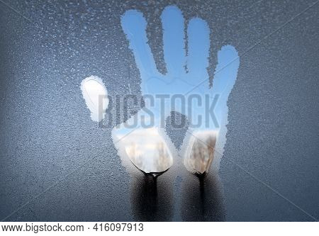 A Palm Mark On The Glass Covered With Ice. The Window Is Covered With Frost With A Trace From The Pa