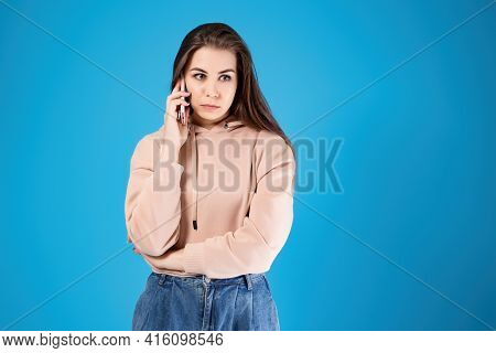 A Young Girl Is Talking On The Mobile Phone. Portrait Of Emotions. Waiting Dial On The Phone Line, C