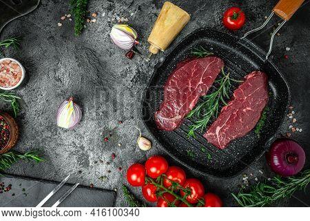 Raw Cap Rump Steak Or Top Sirloin Beef Meat Steak Oon A Grill Pan On Black Background. Top View.
