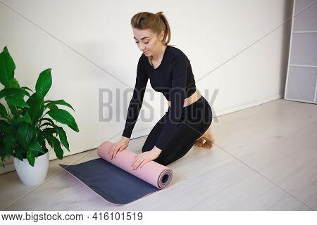 Woman Unfold Yoga Mat Preparing For Practice.