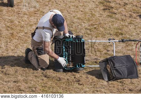 Man Gardener Cleaning The Machine Scarifier From Old Dry Grass On The Lawn
