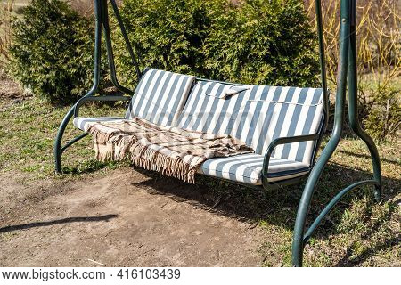 Swing Bench In Lush Garden. Curved Swing Bench Hanging From The Bough Of A Tree In A Lush Garden Wit