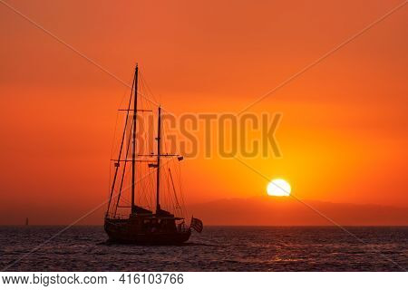 Silhouette Of Sailing Boat With Sails Down Against Sun At Sunset, Sun Glare On Sea Waters. Romantic