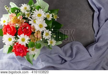 Top View. Greeting Card. Bouquet Of Flowers And Folds Of Blue Fabric On A Dark Background