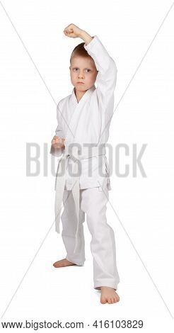Little Boy In Kimono Stands In Karate Rack Isolated On White Background
