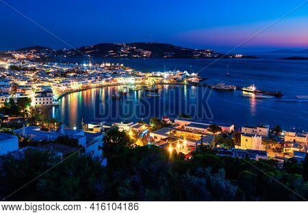 Beautiful Night View Of Mykonos, Greece, Ships, Port, Whitewashed Houses. Town Lights Up. Vacations,
