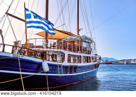 Sailboat Under Greek Flag Moored At Jetty Of Typical Greek Island. Schooner. Summer Day Sunshine, Va