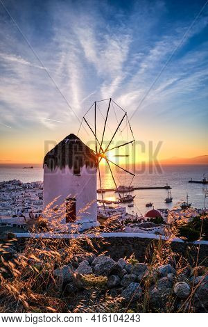 Famous Traditional White Windmill Overlook Port And Harbor Of Mykonos, Cyclades, Greece At Sunset Sk