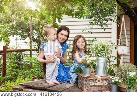 Young Delighted Mother Sitting In Armchair With Adorable Little Siblings On Terrace Of Country House