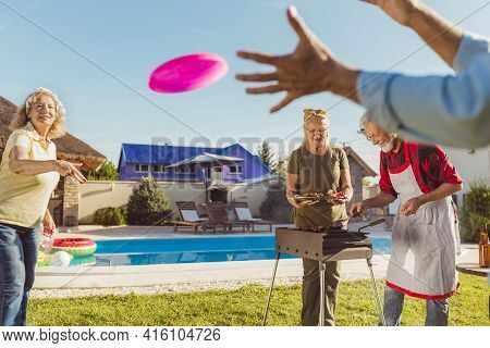 Group Of Cheerful Active Senior People Having A Backyard Barbecue Party, Grilling Meat And Vegetable
