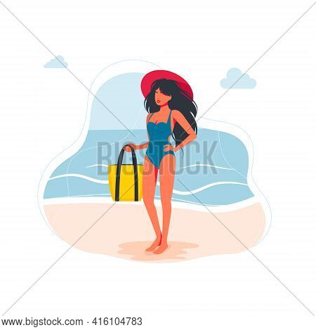 Slender Woman Dressed In Swimsuit With Big Hat At Her Head Is Standing On The Beach, Holds A Bag In