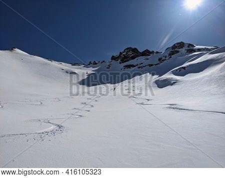 Man Skier Rides Through Powder Snow To The Mountains. Winter Sports Freeride. Etscherzapfen In Glaru