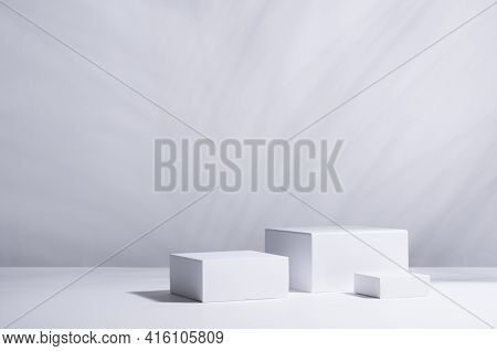 Fashion Modern Summer Abstract Showcase With White Square Podiums In Sunlight With Shadow Palm Leaf