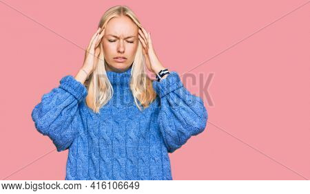 Young blonde girl wearing wool winter sweater suffering from headache desperate and stressed because pain and migraine. hands on head.