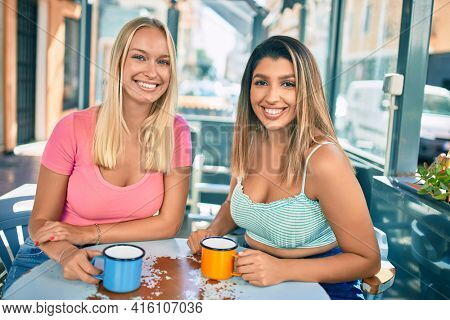Two beautiful and young girl friends together having fun at cafeteria