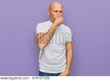 Bald man with beard wearing casual white t shirt smelling something stinky and disgusting, intolerable smell, holding breath with fingers on nose. bad smell