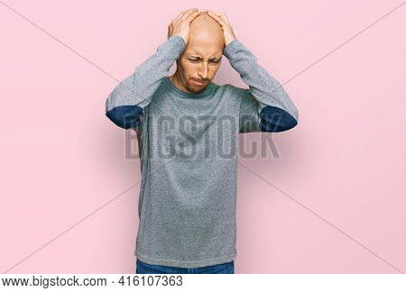 Bald man with beard wearing casual clothes suffering from headache desperate and stressed because pain and migraine. hands on head.