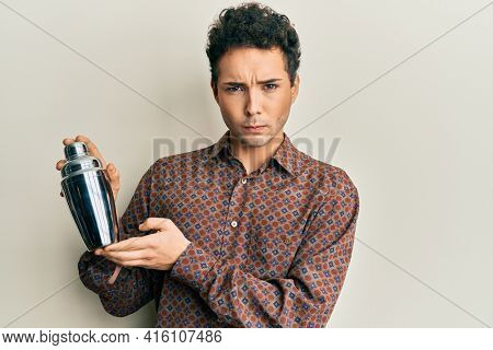 Young handsome man preparing cocktail mixing drink with shaker skeptic and nervous, frowning upset because of problem. negative person.