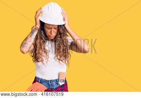 Young hispanic woman with tattoo wearing hardhat and builder clothes suffering from headache desperate and stressed because pain and migraine. hands on head.
