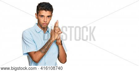 Young handsome african american man wearing casual clothes holding symbolic gun with hand gesture, playing killing shooting weapons, angry face