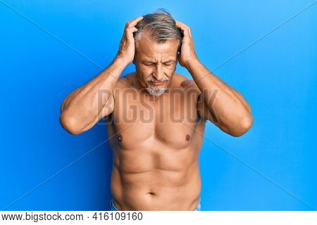 Middle age grey-haired man standing shirtless suffering from headache desperate and stressed because pain and migraine. hands on head.