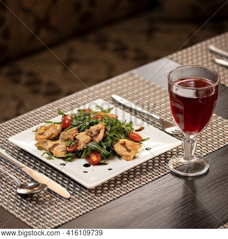 Tasty Appetizer Of Arugula, Cherry Tomato And Fried Bacon On Served Restaurant Table With Glass Of R