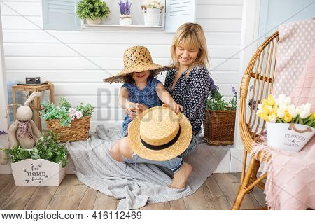 Little Girl Of 4-5 Years Old Is Playing With Straw Hats On Veranda Of House With Her Mother In Arms.