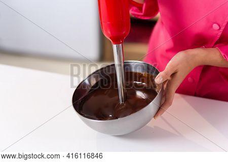 A Red Blender Mixes Liquid Dark Chocolate. Chef Hands, No Face