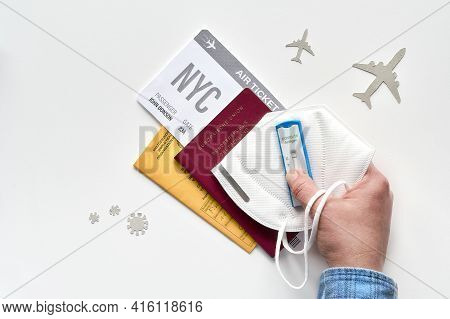 New Normal Travel During Covid-19 Restrictions, Flat Lay On White Background. Hand Hold German Passp