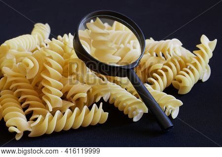 Durum Wheat Spiral Pasta And A Magnifying Glass Lie On A Dark Background. Concept For Research, Anal