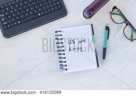 We Are Hiring. Job Recruting Concept. Words We Are Hiring In Notebook On The Working Table. Top View