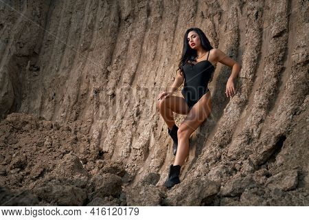 Gorgeous Dark-haired Woman In Stylish Black Bodysuit Standing On Fresh Air Among Dry Quarry. Beautif