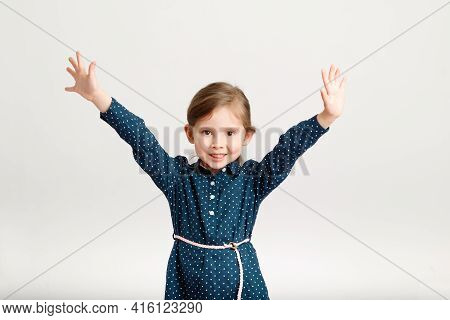 Little Cute Happy Smiling Girl 4-6 Years Old Wearing A Blue Dress With Polka Dots Standing With Hand