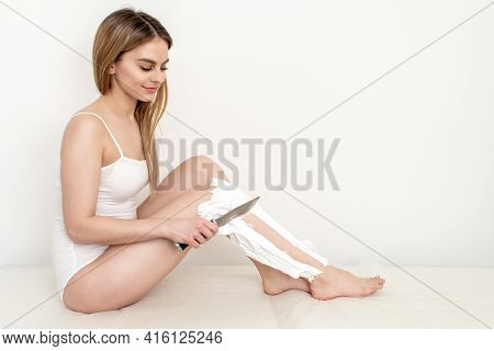 Beautiful Woman Shaves Her Legs By A Knife Smeared With Shaving Foam On White Background. Depilation