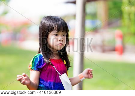 Emotional Of Kid Concept. Girl Is Wondering Something. Cute Child Hanging A Mask On Her Neck. Asian