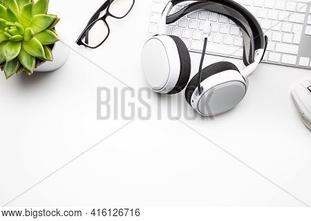 Home Office Desk Workspace With Headphones, Glasses, Coffee And Keyboard On White Background, Top Vi