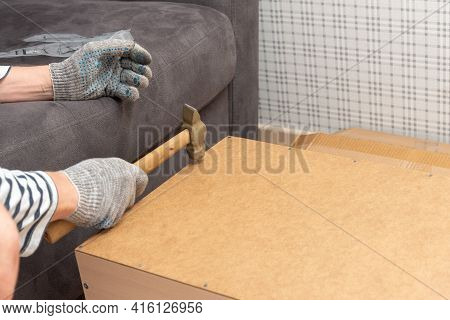 Male Hands In Gloves Hold A Hammer And Hammer In A Nail. Home Furniture Assembly, Home Office Booksh