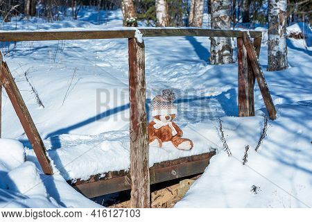 A Soft Toy Teddy Bear Wearing A Scarf And A Hat Sits On Snow Covered Wooden Bridge In The Winter For