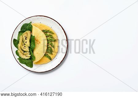Omelette Or Omelet Stuffed With Asparagus, Avocado And Spinach Leaves For Breakfast Isolated On Whit