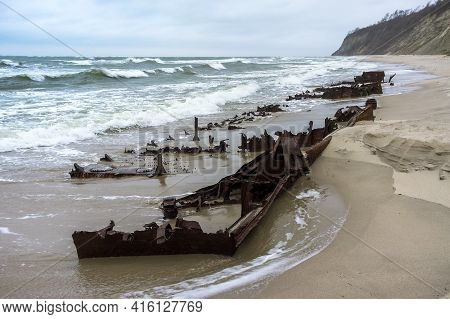 The Rusted Wreckage Of An Old Ship. The Remains Of A Seagoing Vessel On The Shore. Old Rusty Ship.