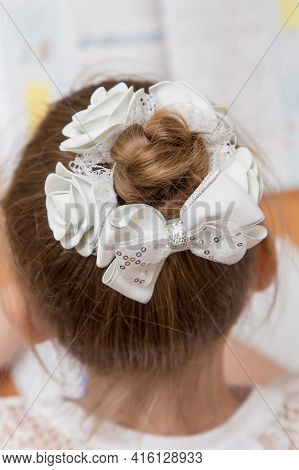 Close-up Of A Girls Hairstyle With A Bun Of Hair Tied With A White Bow. Hair Styling Is Done With A